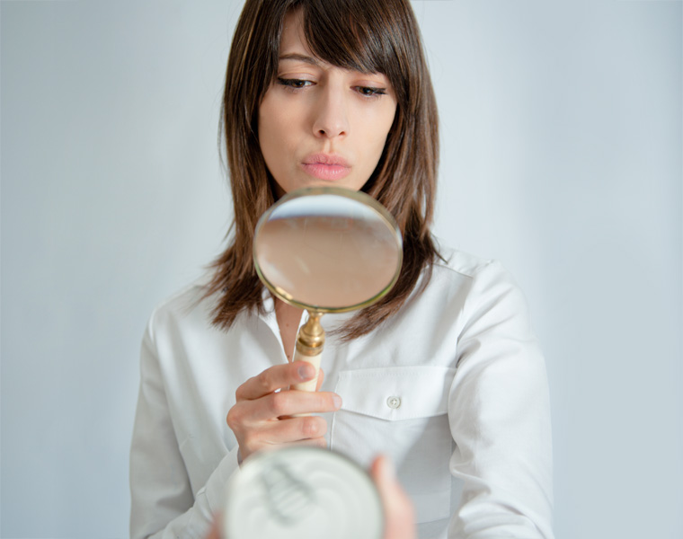 Frau nimmt Zutatenliste unter die Lupe
