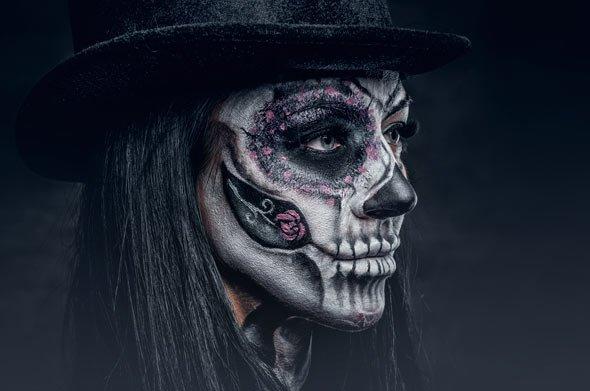 Viele dunkle Farben im Gesicht und am Körper zeichnen ein unheimliches Skelett Kostüm aus