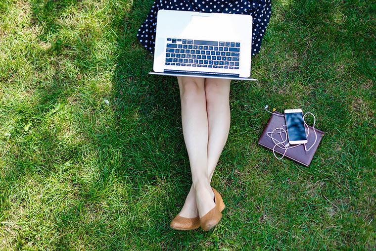 Frau mit Laptop auf Wiese