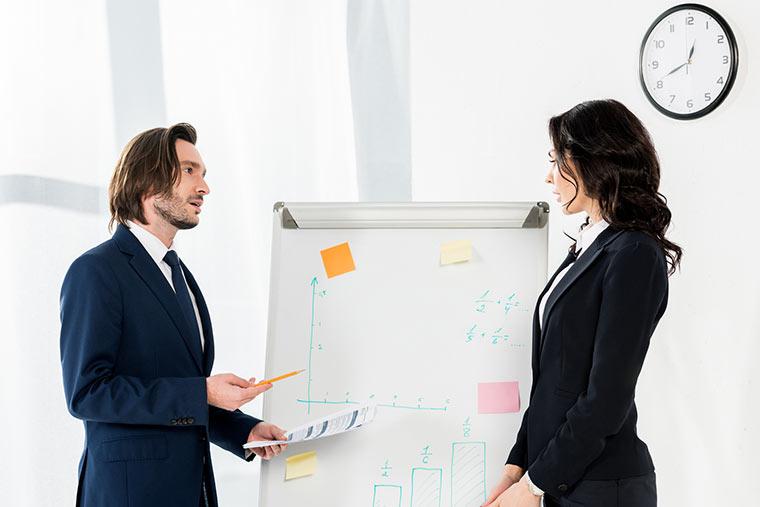 Geschäftsmann und Geschäftsfrau vor Flipchart