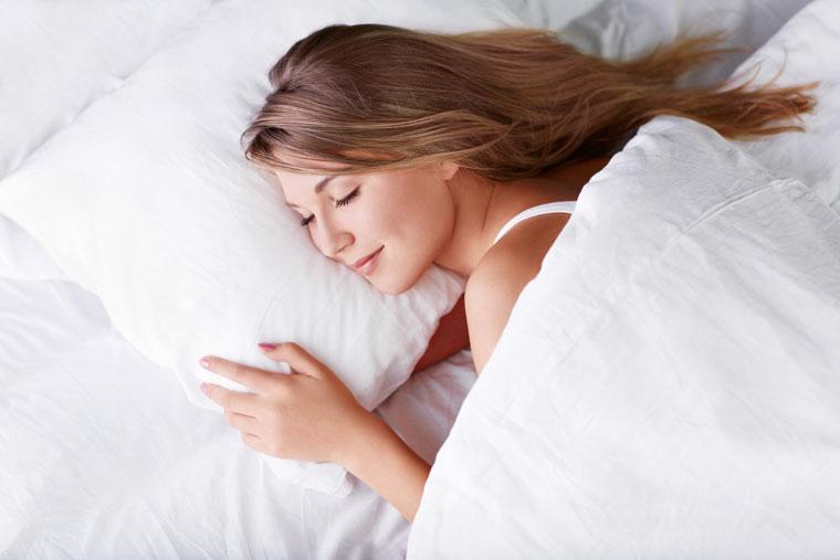 Frau schläft in Bio Daunen Decke