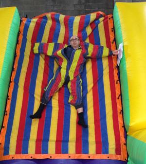 Adam Shaw hängt  an einer Wand in einem regenbogenfarbenen Anzug in einer leeren Lagerhalle