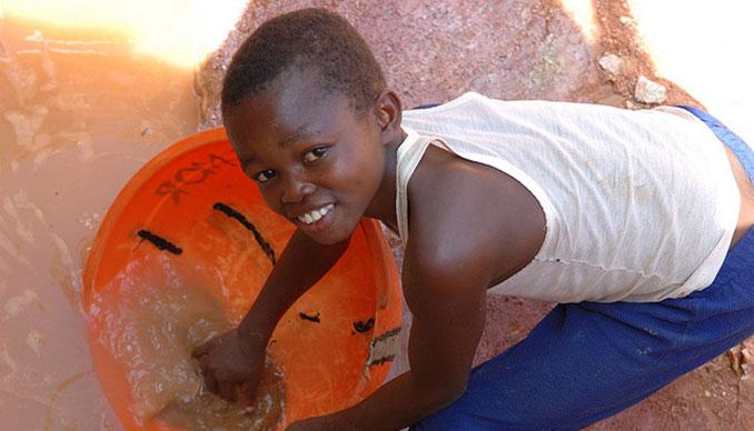 Kind mit rotem Wassereimer