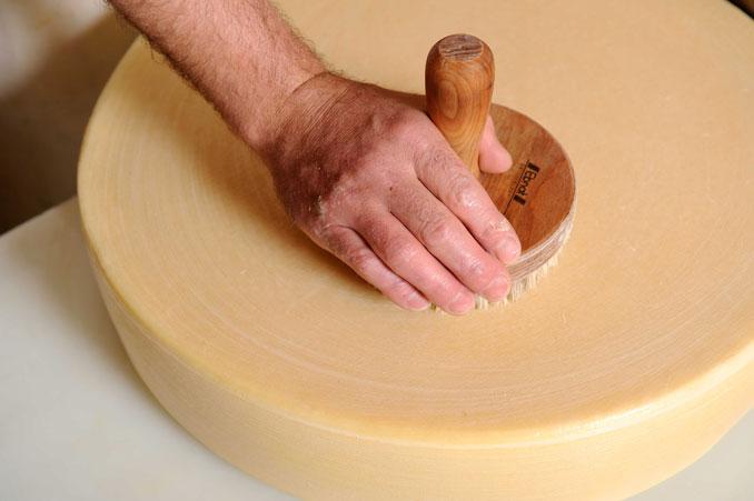 Ein Laib Käse wird bearbeitet
