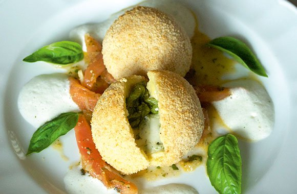 Gebackene Mozzarellaknödel auf geschmolzenen Tomaten