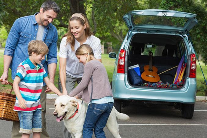 Familie mit Hund fährt in Urlaub und macht ein Picknick
