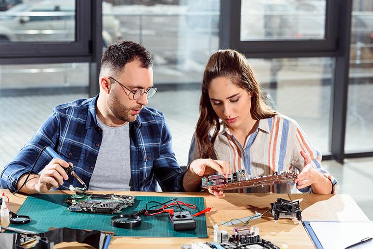 Frau und Mann reparieren Platine