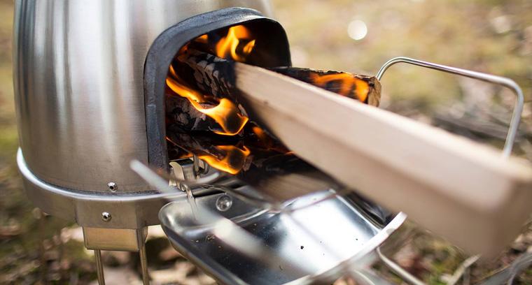 Dieser Grill grillt mit Holzkohle und ist mit einem batteriebetriebenen Heizungs-Ventilator ausgestattet.