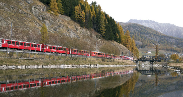 Die Rhätische Bahn spiegelt sich in einem klaren Bergsee
