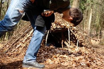 Eine Hütte aus Stöcken und Laub sorgt für die nötige Trockenheit und Wärme zum Überleben © Wildnisschule Teutoburger Wald