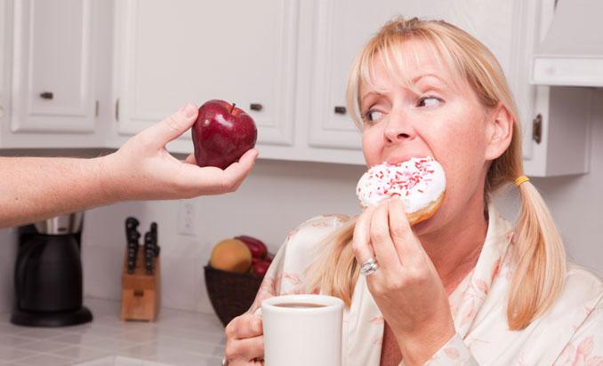 Frau isst lieber Donut als Apfel