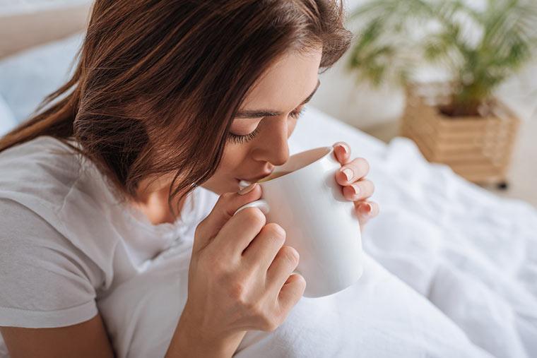 Frau trinkt eine Tasse Tee im Bett