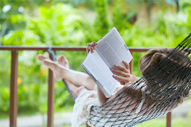 Frau liest ein Buch in ener Hängematte