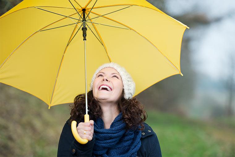 Gesunde Frau hält einen gelben Regenschirm