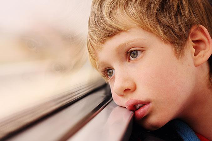 Junge guckt traurig aus dem Fenster
