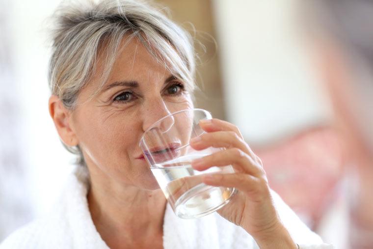 Ältere Frau trinkt ein Glas Wasser