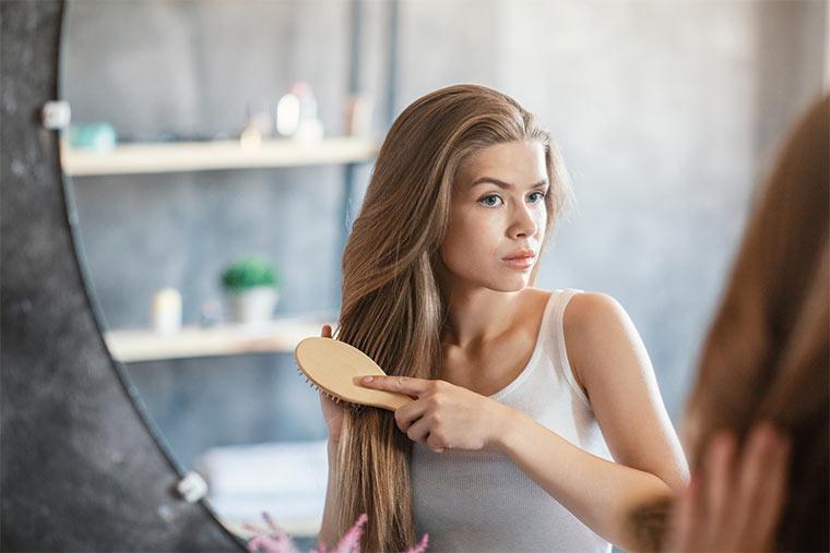 Frau bürstet Haare mit Holzbürste