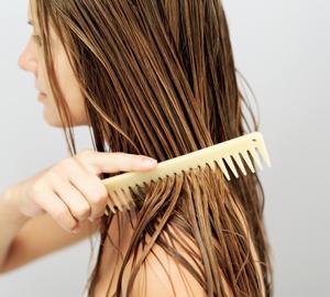 Für eine wohltuende Haarmaske gibt man einen großzügigen Klecks Kokosnussöl auf die Hände und zieht das Öl strähnchenweise durch die nassen Haare.
