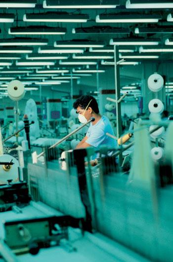 Gesichtsmaske gegen giftige Farbstoffdämpfe und Bleichmittel sind nicht üblich in den Textilfabriken der Welt ©Medioimages/Photodisc