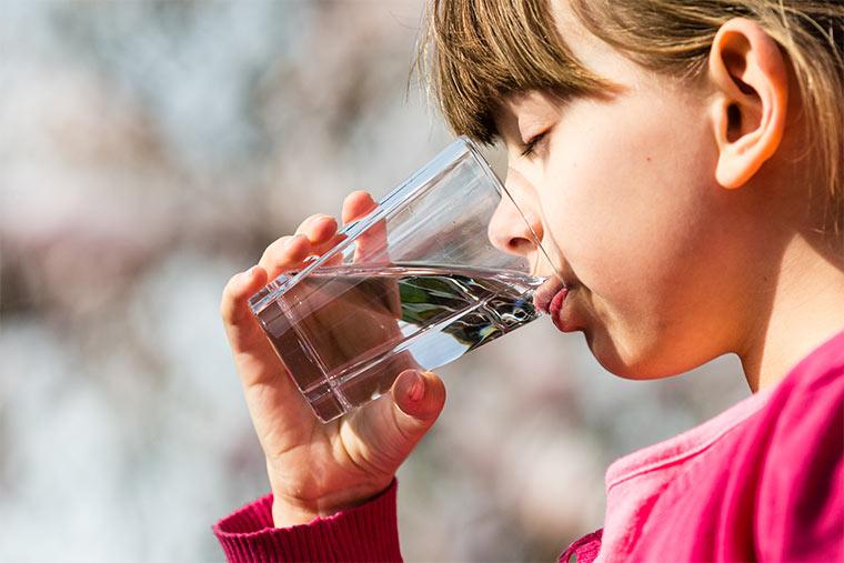 Mädchen trinkt Glas Wasser