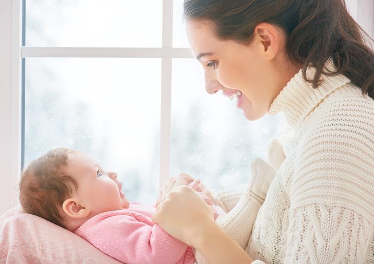 Glückliche Mutter mit Baby vor dem Fenster.